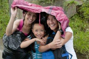 Kolumbien, zwei Frauen und ein Mädchen unter Regenjacke, Latin America Tours